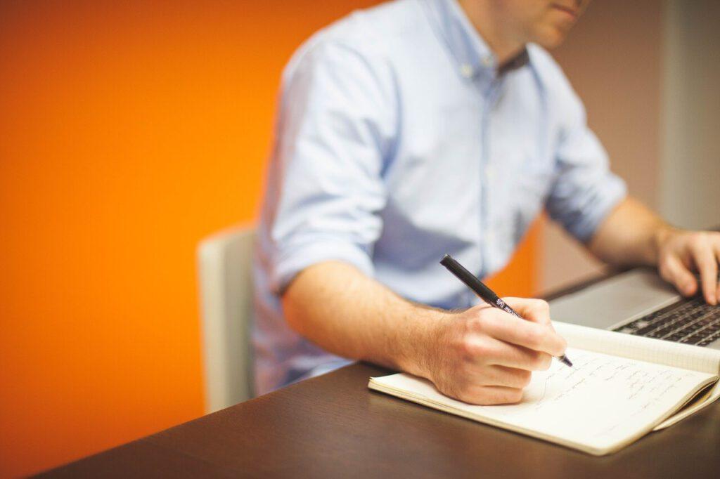 Mann macht sich Notizen von einem Computer